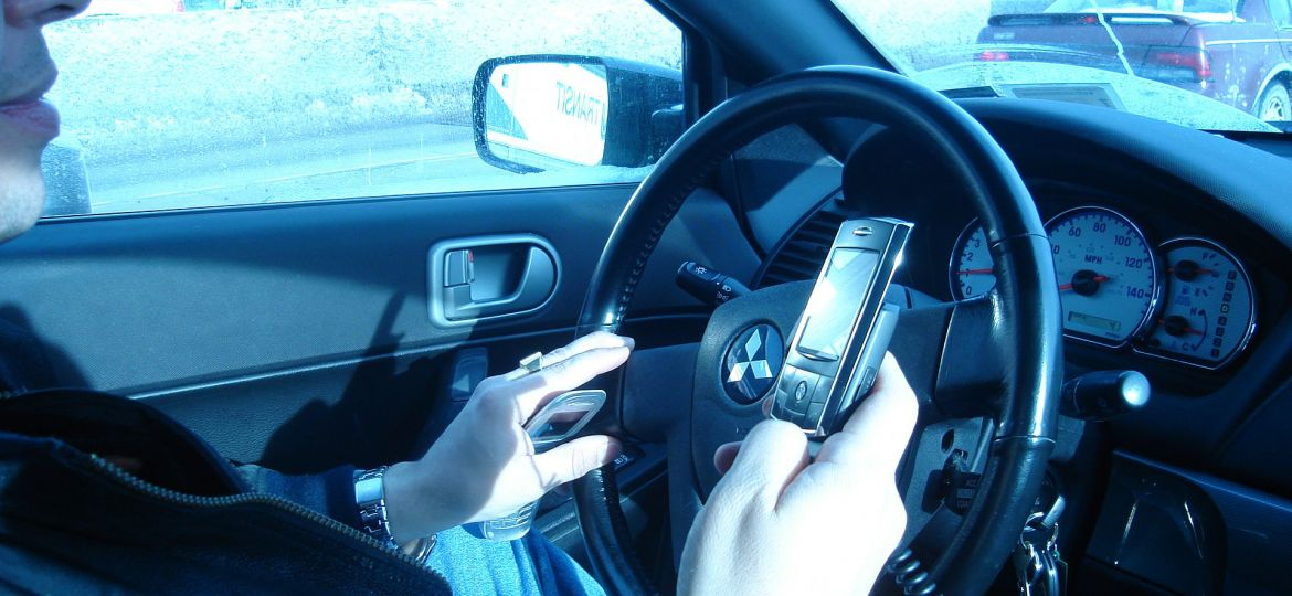 1920px-Hand_held_phone_in_car